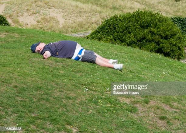 Overweight man asleep on the grass, UK.