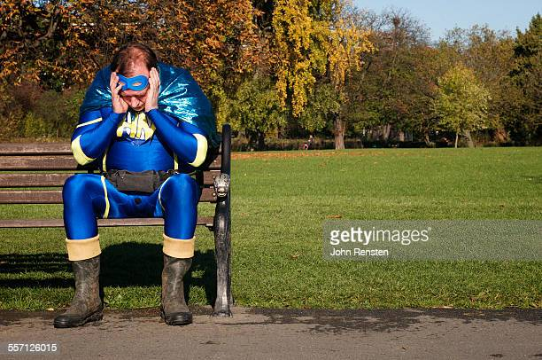 Overweight Man Dressed as Hero Sitting on Bench