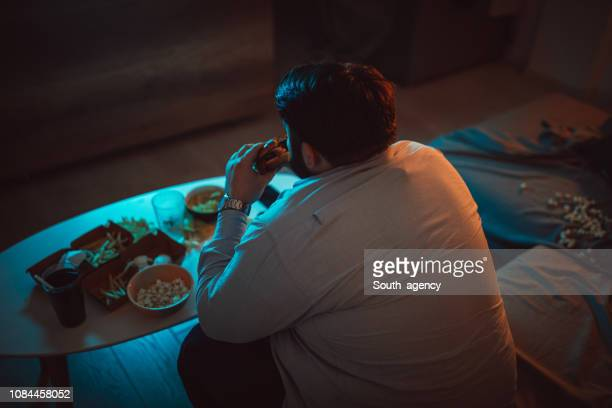 overweight man eating a burger - over eating stock pictures, royalty-free photos & images