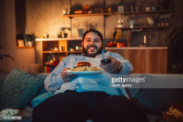 overweight man eating fast food and watching television - unhealthy living stock pictures, royalty-free photos & images