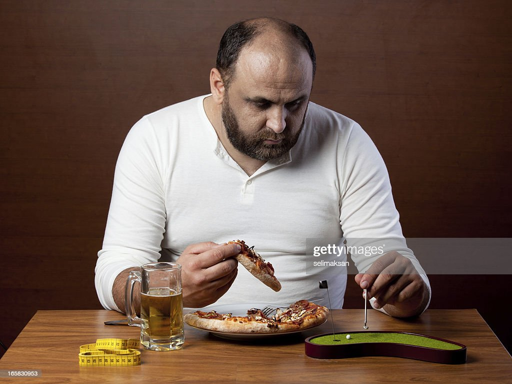 Overweight man eating pizza and doing lazy sport : Stock Photo