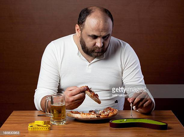 overweight man eating pizza and doing lazy sport - ugly bald man stock photos and pictures