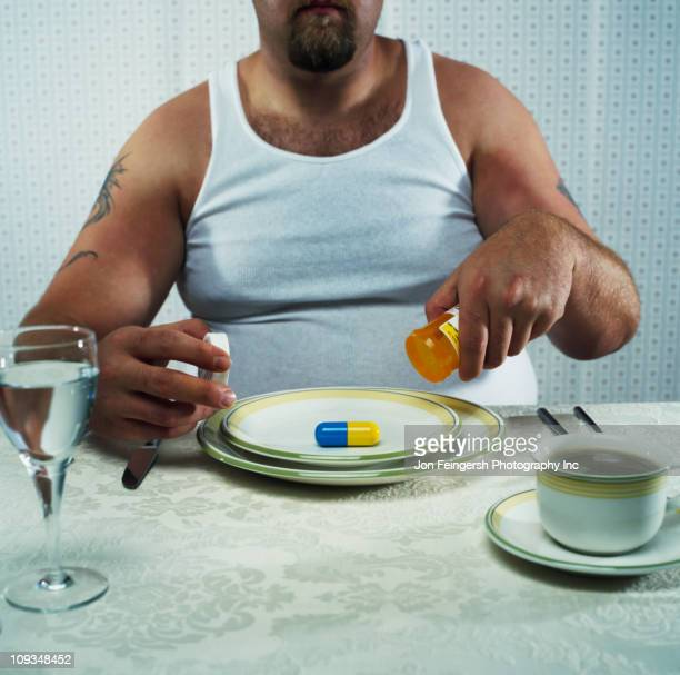 Overweight man emptying large pill from pill bottle