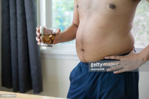 overweight man holding glass of aerated soft drink - lap body area stock photos and pictures