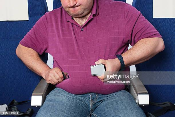 overweight man in an airplane - chubby men stock photos and pictures