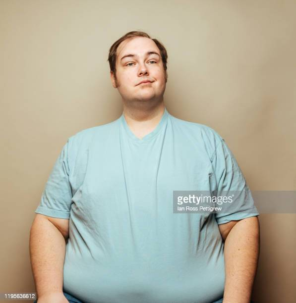overweight man in blue shirt making faces - chubby stock pictures, royalty-free photos & images