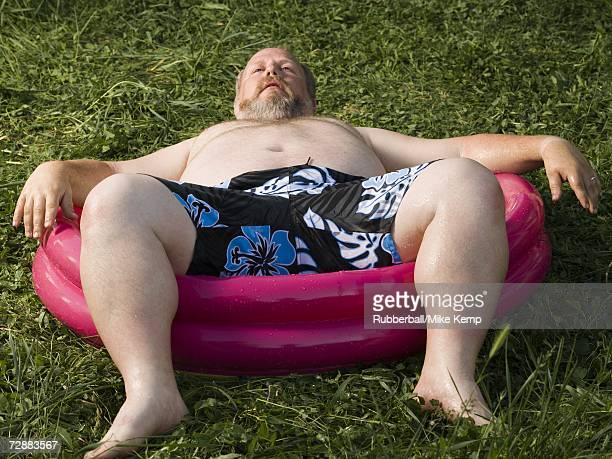 overweight man in inflatable wading pool - homme gros ventre photos et images de collection