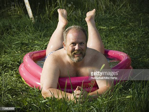 Overweight man in inflatable wading pool