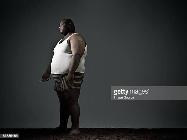 Overweight man in underwear watching tv