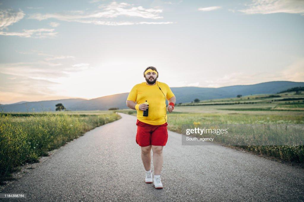 夕暮れ時に路上でジョギングをする太りすぎの男 : ストックフォト