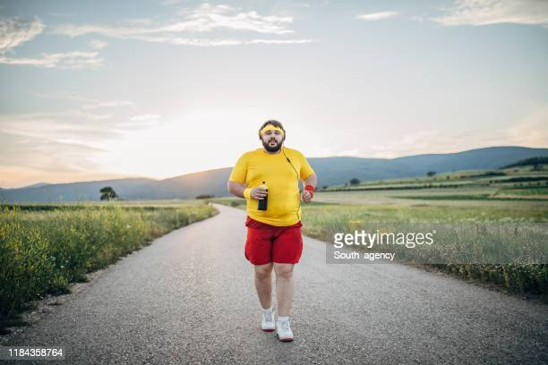 overweight man jogging on the street in sunset - heavy stock pictures, royalty-free photos & images