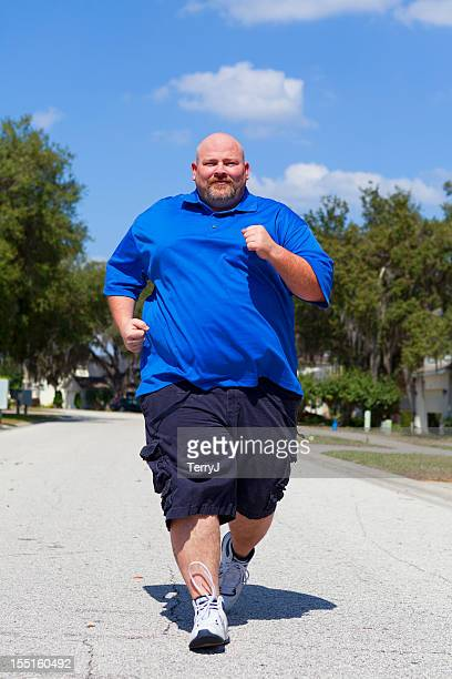 overweight man jogs down the street - fat bald men stock pictures, royalty-free photos & images