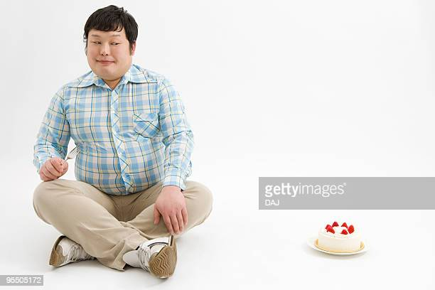 Overweight man looking at a cake