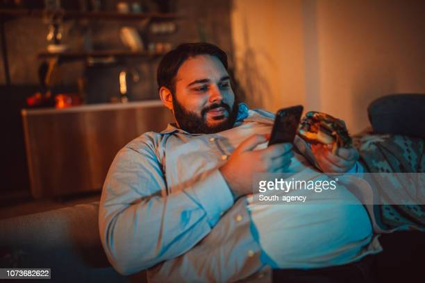 overweight man looking at the phone - ciccione foto e immagini stock