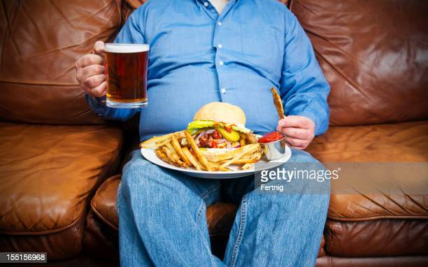 overweight man over-eating on a couch - unhealthy living stock pictures, royalty-free photos & images