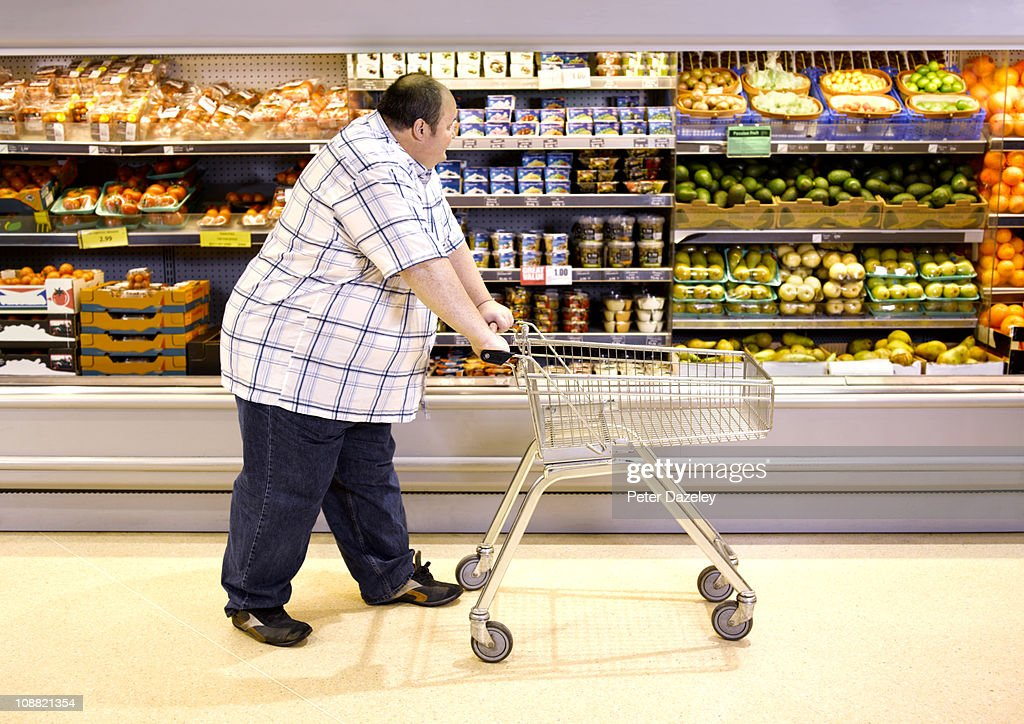Overweight man passing by healthy food : ストックフォト