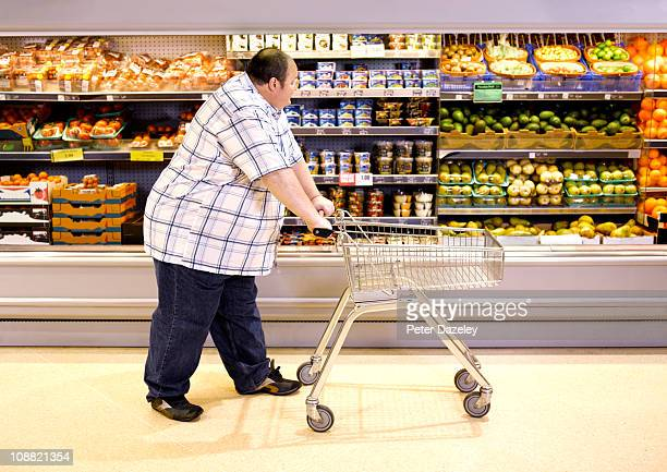 Overweight man passing by healthy food