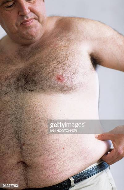 overweight man pinching fat on waist - hairy chest stock photos and pictures