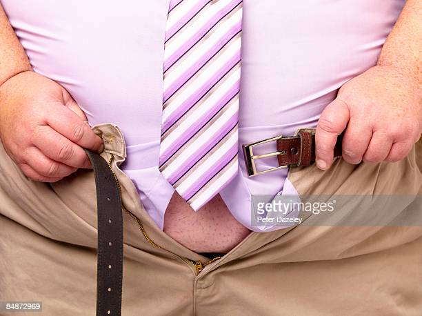 Overweight man pulling trousers together