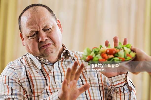 overweight man refusing salad. - weigeren stockfoto's en -beelden