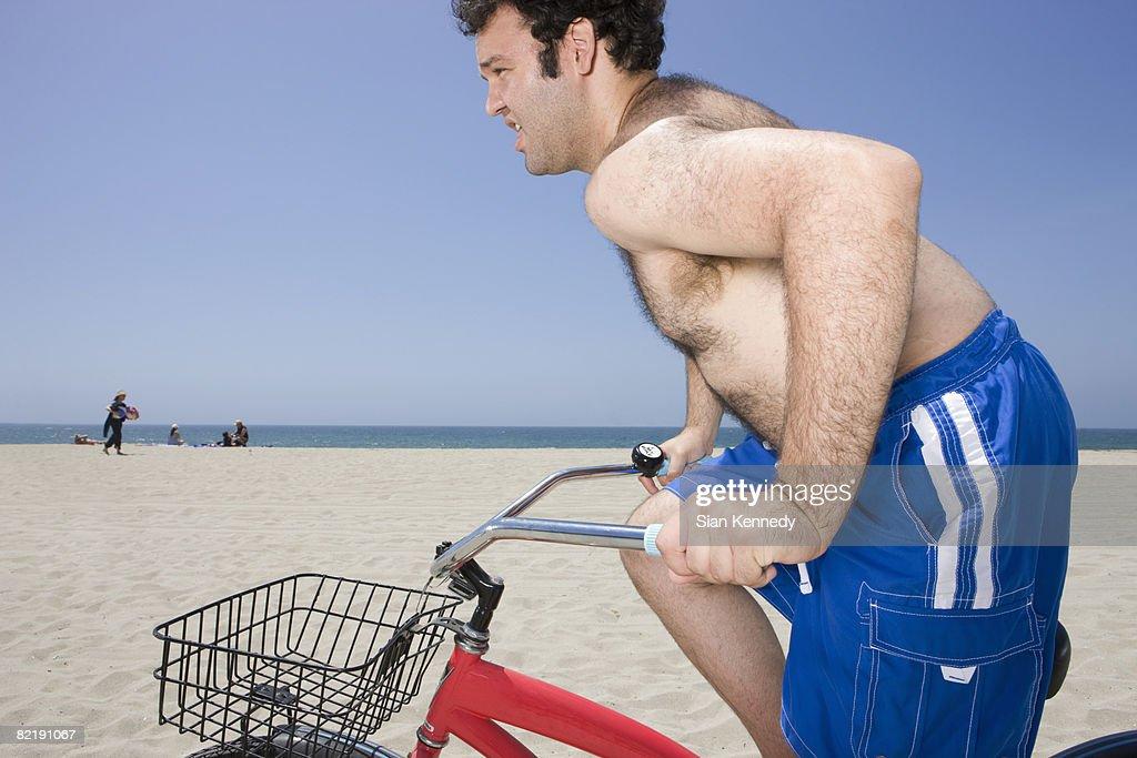 Overweight man riding bike on the beach : Stock Photo