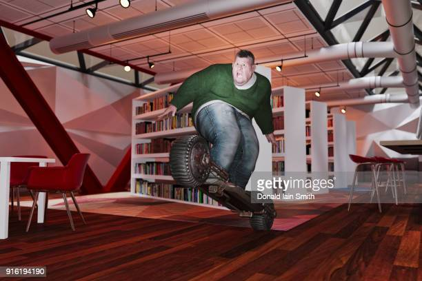 Overweight man riding futuristic skateboard in library
