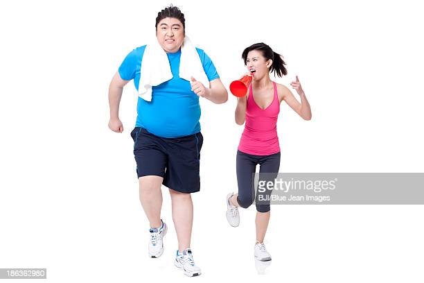 Overweight man running with young woman's support