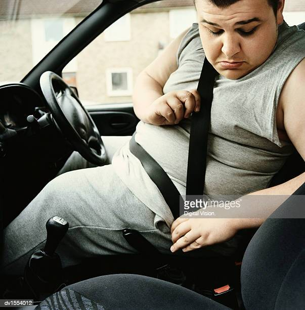 overweight man sits in the drivers seat of a car looking down as he fastens his seatbelt - befestigen stock-fotos und bilder