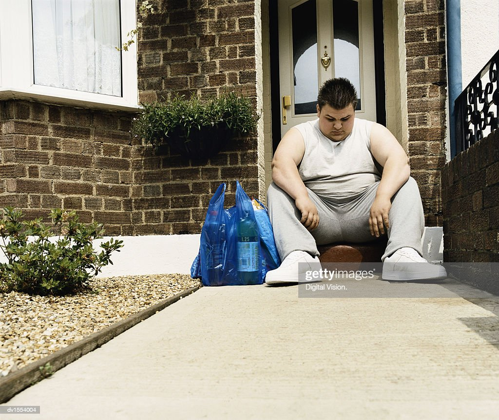 Overweight Man Sits Next to His Shopping on a Doorstep : Stock Photo
