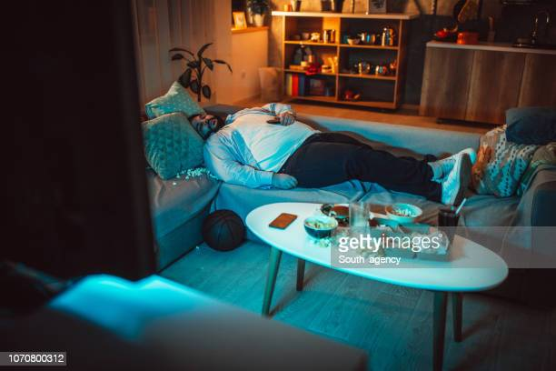 overweight man sleeping on sofa in a messy room - laziness stock pictures, royalty-free photos & images