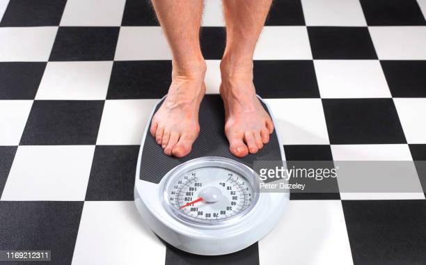 overweight man standing on bathroom scales - one man only stock pictures, royalty-free photos & images