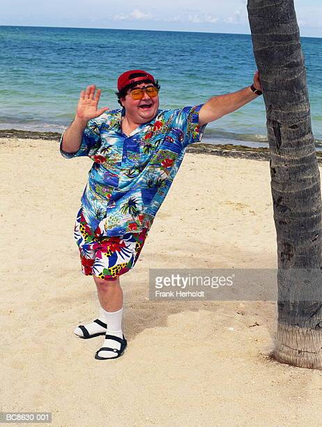 overweight man standing on beach, leaning on palm tree, waving - fat man on beach stock photos and pictures