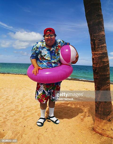 Overweight man standing on beach, wearing inflatable ring, portrait