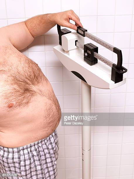 Overweight man standing on scale