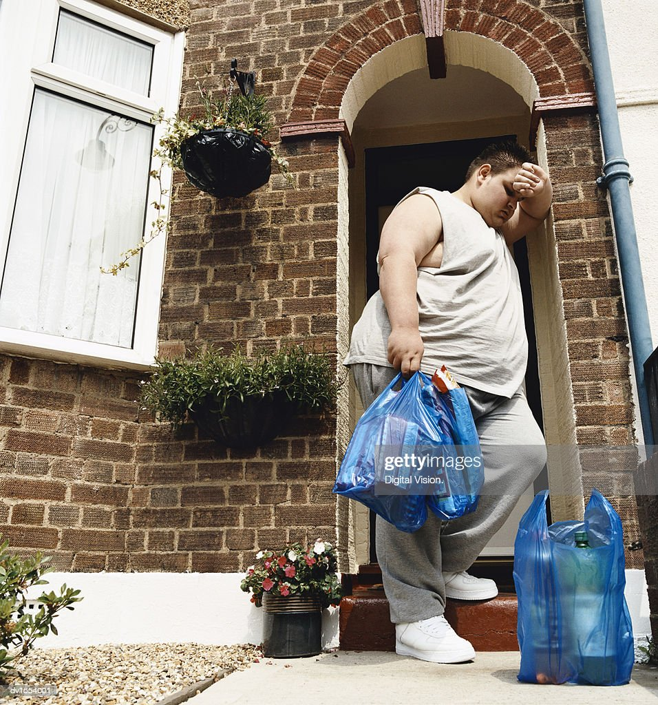 Overweight Man Stands at His Front Door With Carrier Bags of Groceries Leaning His head on His Arm : Stock Photo