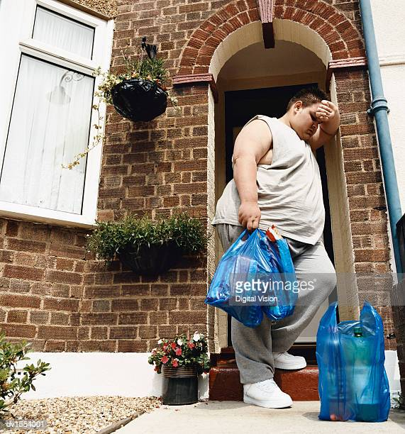 Overweight Man Stands at His Front Door With Carrier Bags of Groceries Leaning His head on His Arm