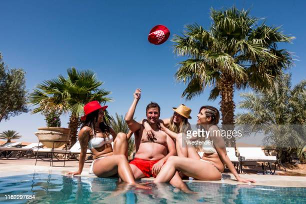 overweight man surrounded by affectionate beautiful women at the poolside - omgeven stockfoto's en -beelden