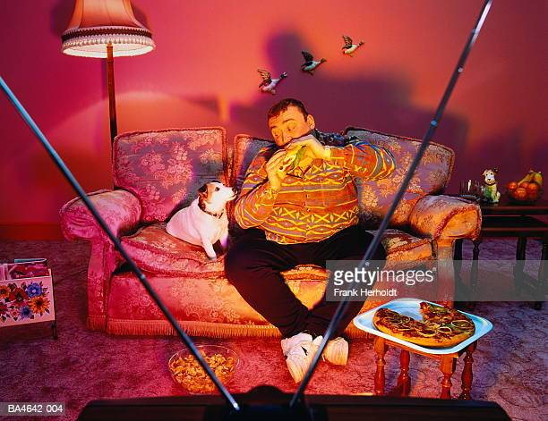 Overweight man surrounded by snacks, eating burger, watching TV