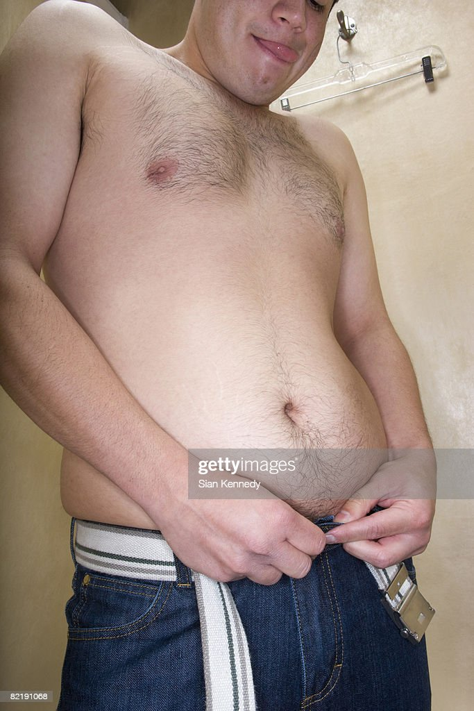 Overweight man trying on clothing : Stock Photo