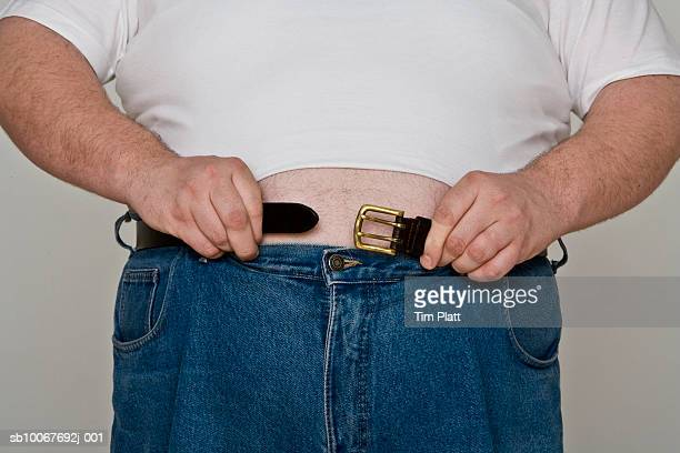 Overweight man trying to buckle a belt