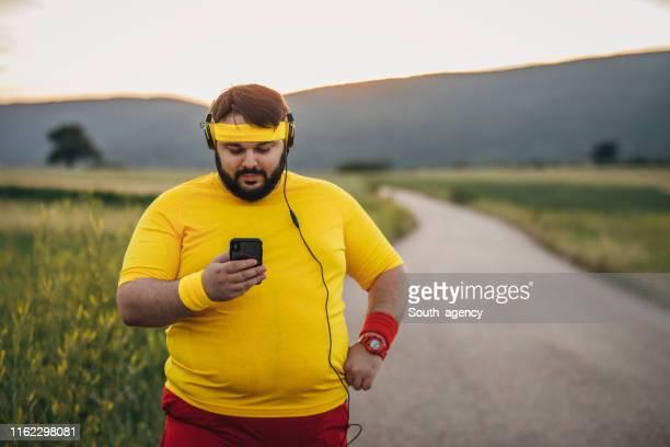 homme de poids excessif utilisant le téléphone intelligent sur la coupure de formation - gras photos et images de collection
