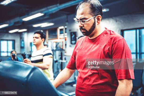overweight man using treadmill at a gym - leisure facilities stock pictures, royalty-free photos & images