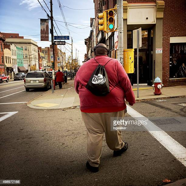 overweight man walking across a street - fat black man stock photos and pictures
