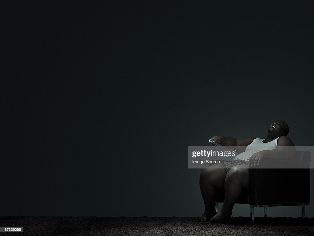 Overweight man watching television : Stock Photo