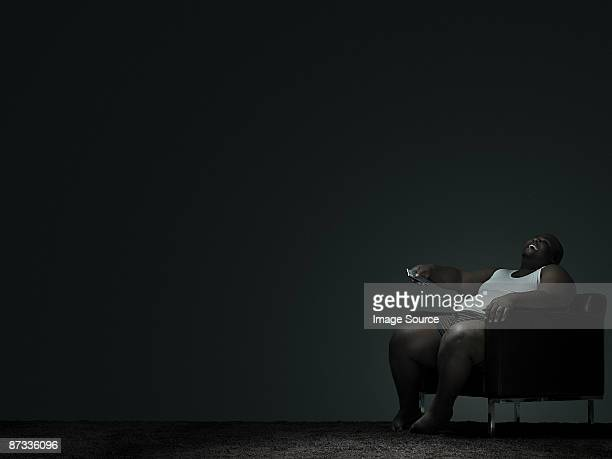overweight man watching television - fat black man stock photos and pictures