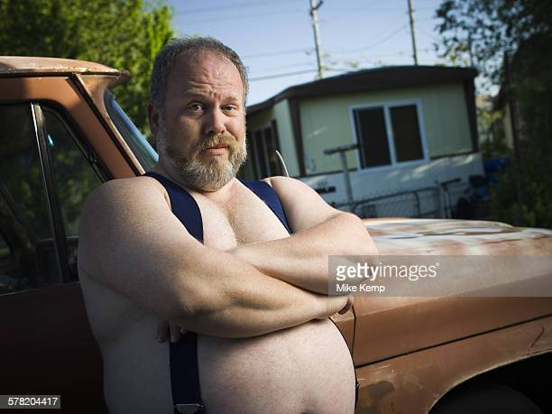 overweight man with suspenders by truck - redneck stock photos and pictures