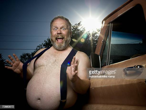 overweight man with suspenders by truck - suspenders stock pictures, royalty-free photos & images