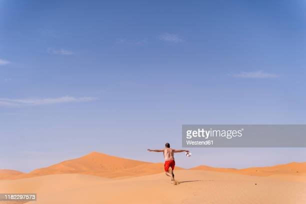 overweight man with swimming shorts running in the desert of morocco - superman stock pictures, royalty-free photos & images