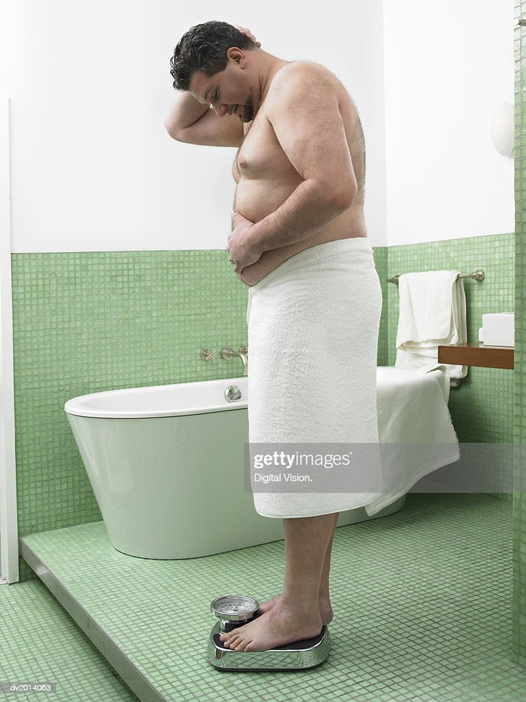 Overweight Man Wrapped in a Towel Stands on a Pair of Scales in a Bathroom : Stock Photo