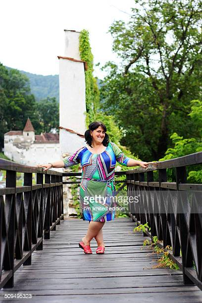Overweight middle aged woman on bridge posing